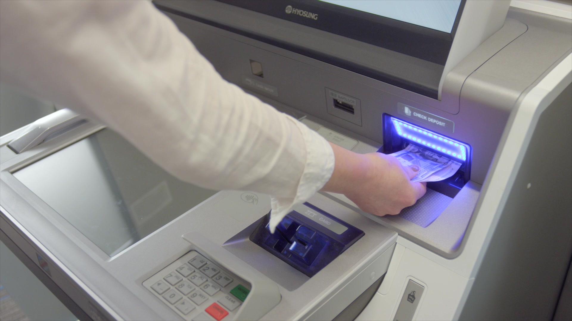 woman insert cash into kiosk to make a loan payment at first alliance credit union