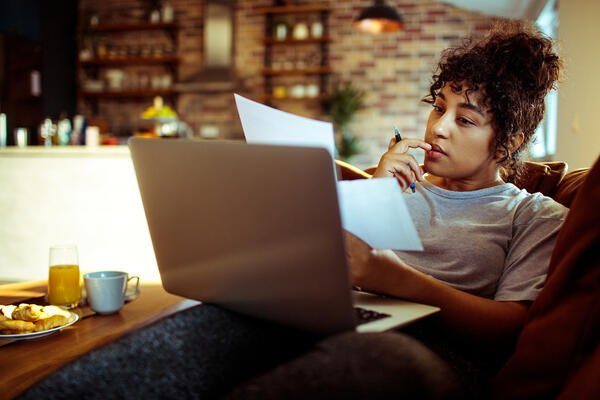 Woman looking thoughtful while budgeting | First Alliance Credit Union